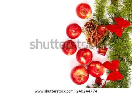 Christmas decoration with green pine or fir and many scattered red apples. Holiday decorations isolated on white background. Empty or copy space for holiday greeting card - stock photo