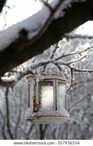 Christmas decoration with lantern, snow and fir tree branch. Candlestick on tree  in winter home garden. - stock photo