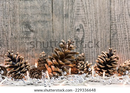 Christmas decoration with lighs and fir cones on wooden background - stock photo