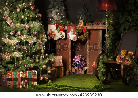 Christmas decoration with new year tree, rocking chair, fire place, gift boxes and teddy bears. Dark christmas ballons are at the new year tree, gold christmas balls and new year lights
