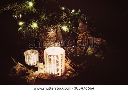 Christmas decoration with pine branches, reindeer and candlelight against a dark background in a subtle retro look - stock photo