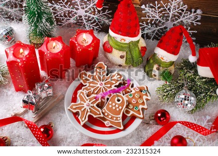 christmas decoration with plate of homemade gingerbread cookies,candles and santa figurines on snow