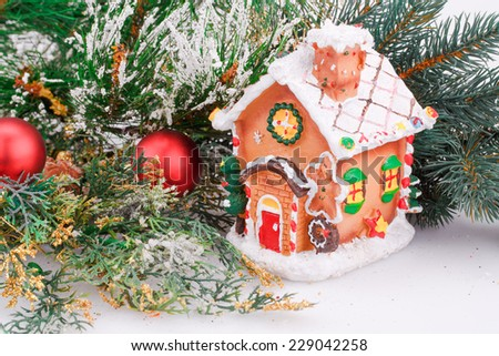 Christmas decoration with red balls, fir-tree branch and toy house. - stock photo
