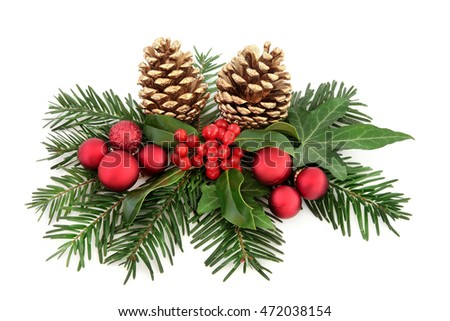 Christmas decoration with red baubles, holly, ivy, gold pine cones and winter greenery over white background.