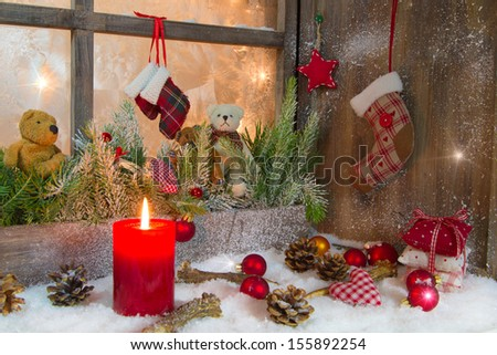 Christmas decoration with red candle on window sill. - stock photo
