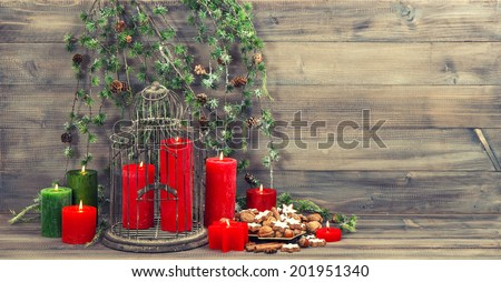 christmas decoration with red candles, birdcage and pine branch. cinnamon cookies, nuts and spices. vintage home interior. retro style toned picture - stock photo
