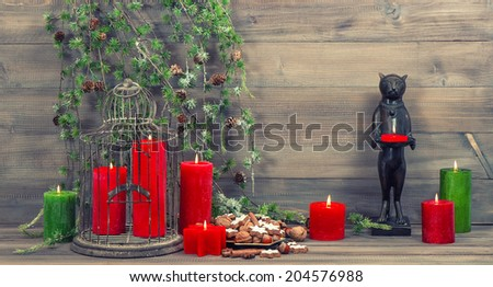 christmas decoration with red candles, birdcage and pine branches. cinnamon cookies, nuts and spices. retro style toned picture - stock photo