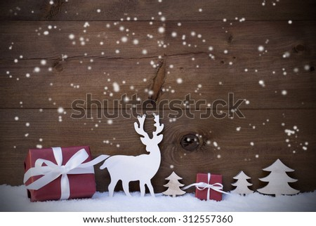 Christmas Decoration With Red Gifts Or Presents Moose Or Reindeer And Christmas Trees On Snow. Card For Seasons Greetings. Copy Space For Advertisement. Snowflakes Infront Wooden Background - stock photo