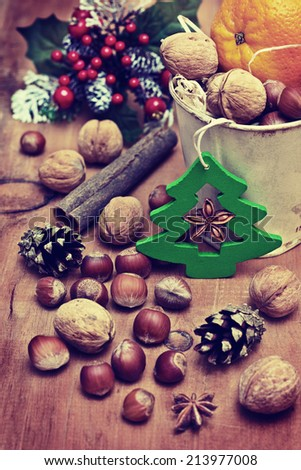 Christmas decoration with spices and nuts on a wooden background - stock photo