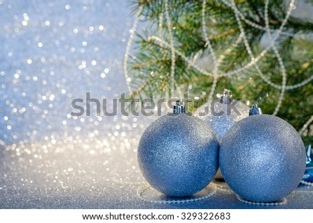Christmas decoration with three silver christmas balls and christmas fir tree branch. Selective focus.