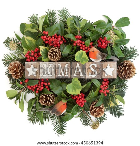Christmas decoration with xmas sign in old wooden blocks, robin decoration, holly, ivy, gold pine cones and fir leaf sprigs over white background. - stock photo