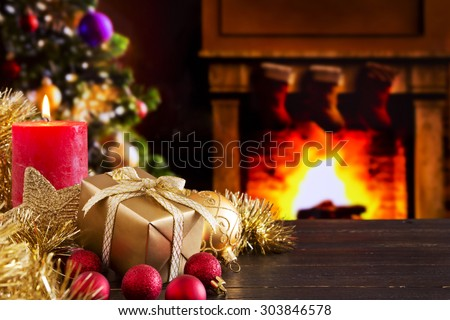 Christmas decorations, a gift and a candle in front of a fireplace. A fire is burning in the fireplace and Christmas stockings are hanging on the mantelpiece. - stock photo