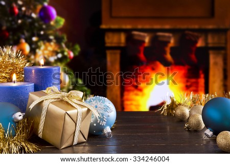 Christmas decorations, a gift and candles in front of a fireplace. A fire is burning in the fireplace and Christmas stockings are hanging on the mantelpiece. - stock photo