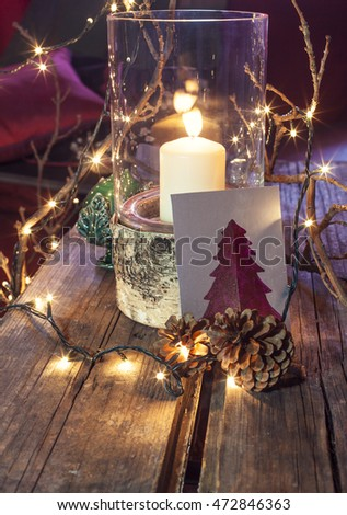Christmas decorations and candle in glass bowl, lights with happy holidays card in foreground