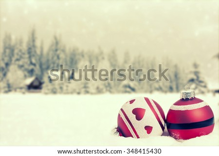 Christmas decorations and gift box in front of snow cowered pine trees  - stock photo