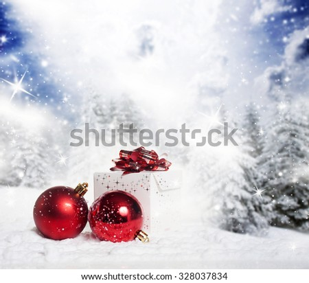 Christmas decorations and gift box in snow - snowy firs in the background - stock photo