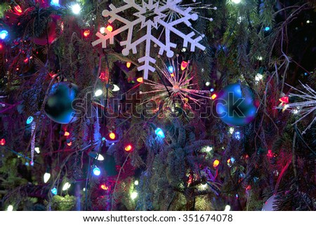 Christmas decorations and lights on a traditional Christmas tree. - stock photo