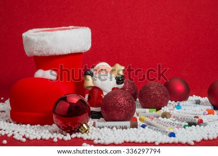 Christmas decorations and oil crayons on red blur background - stock photo