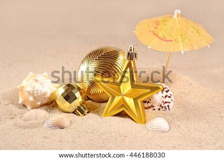 Christmas decorations and seashells on a beach sand - stock photo