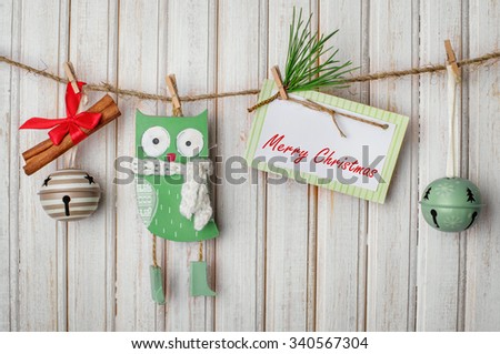 Christmas decorations and toys on a rope with clothespins and tablet for text on wooden background - stock photo