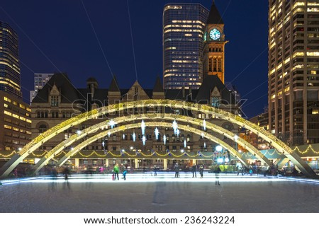 Christmas decorations at Nathan Phillips Square in Toronto and people skating in a free city outdoors rink. Christian joy of Christmas in the melting pot that Toronto is - stock photo