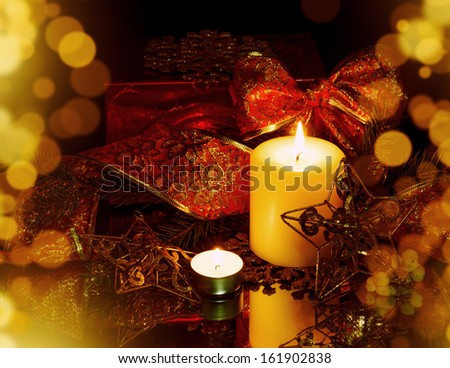 Christmas Decorations background - star, two candles and ribbon on fir tree branch - stock photo