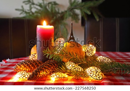 Christmas decorations- candlelit dining room table with Eiffel Tower, orange and christmas tree. - stock photo