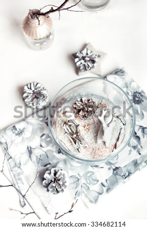 Christmas decorations: ceramic reindeer in silver and white colours in glass jar set with pine cones and dry wigs. Natural light photo. Toned. Shallow focus. - stock photo
