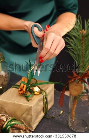 Christmas decorations, Christmas.Woman packs a Christmas gift and decorating the house with Christmas decorations  - stock photo