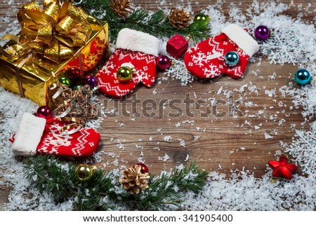 Christmas decorations. Fir branches with gifts and decorations covered with snow - stock photo