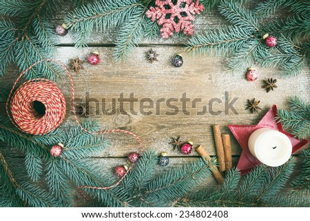Christmas decorations: fur-tree branches, colorful glass balls, a candle, red glittering snowflake, cinnamon sticks and anise stars on a rough wooden background with a copy space - stock photo