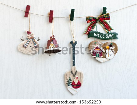 Christmas decorations hanging from a rope. White wood background. Merry Christmas. - stock photo