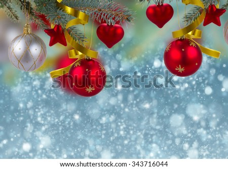 christmas decorations hanging on fir tree border on blue snow background - stock photo