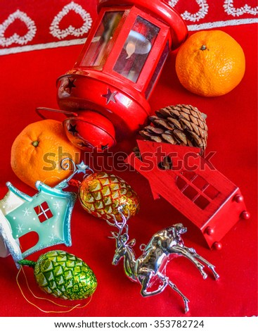 Christmas decorations in mess on red tablecloth - stock photo