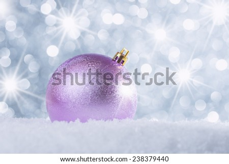 Christmas decorations in snow against abstract background with star luminous effect - stock photo
