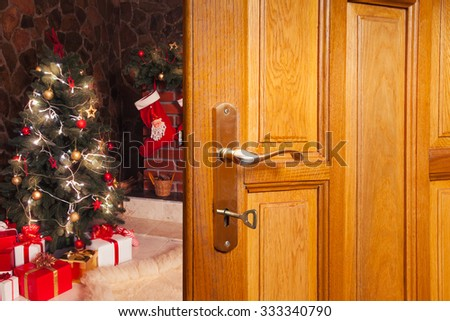 Christmas decorations in the room and opened door - stock photo
