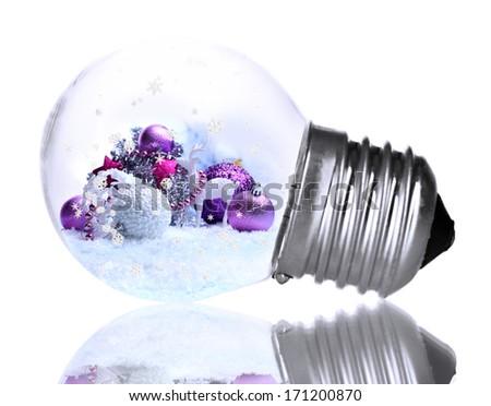 Christmas decorations inside light bulb isolate on white - stock photo