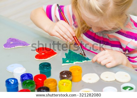Christmas decorations. little girl made and painted the heart  - stock photo