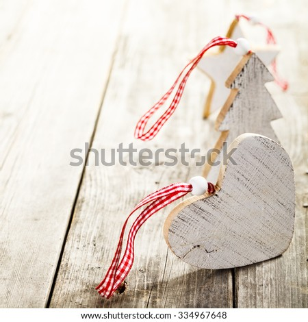 Christmas decorations made of wood with rope standing on wooden background - stock photo