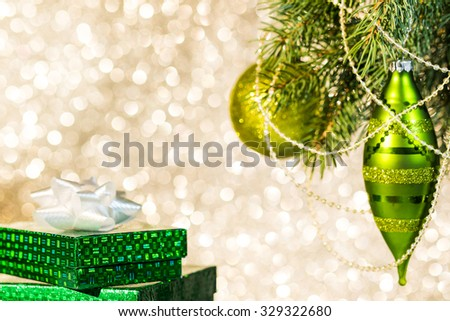 Christmas decorations on a Christmas tree branch and gift boxes over blurred shiny background. Space for text.