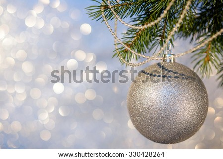 Christmas decorations on a Christmas tree branch over blurred shiny background, close up. Space for text. Selective focus.