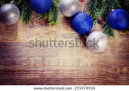 Christmas decorations on a dark wood background. tinting. selective focus on the left bottom light ball - stock photo