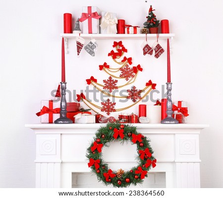 Christmas decorations on mantelpiece on white wall background