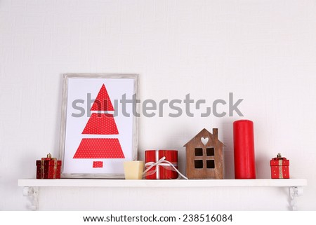 Christmas decorations on mantelpiece on white wall background - stock photo