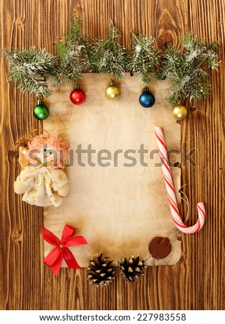 Christmas decorations on the old sheet of paper on a wooden background, place for text - stock photo