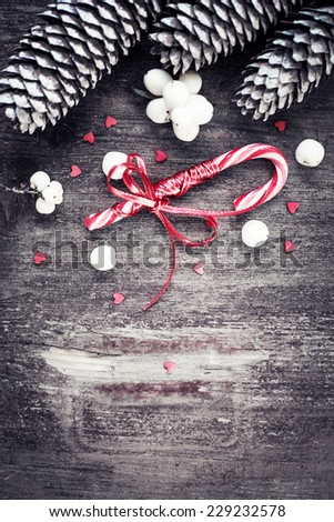 Christmas decorations red and white candy canes on textured wooden background - stock photo