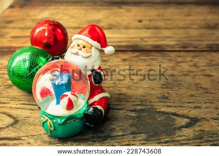 Christmas decorations ,Santa Claus with snow balls  on wooden background. vintage color tone - stock photo