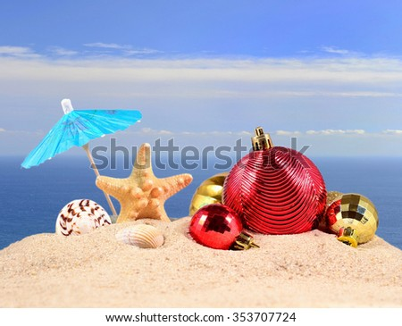 Christmas decorations, seashells and starfish on a beach sand against the background of the sea - stock photo