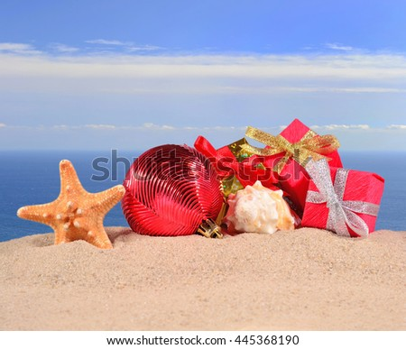 Christmas decorations seashells and starfish on a beach sand against the background of the sea - stock photo