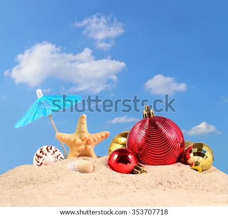 Christmas decorations, seashells and starfish on a beach sand against the blue sky  - stock photo
